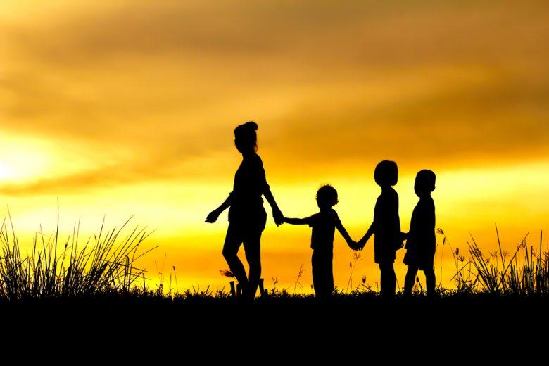 Het silhouette van een moeder en drie kinderen die richting de zonsondergang lopen